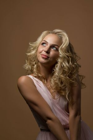 portrait of beautiful curly blonde shy woman in gorgeous pink dress on gold background