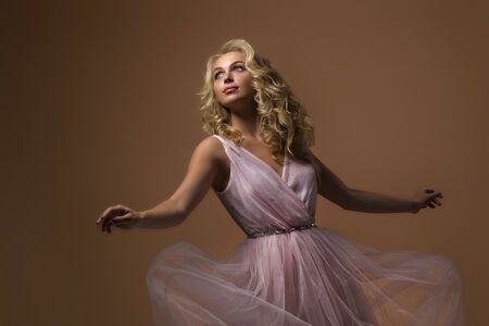 portrait of beautiful curly blonde woman in gorgeous pink dress on gold background