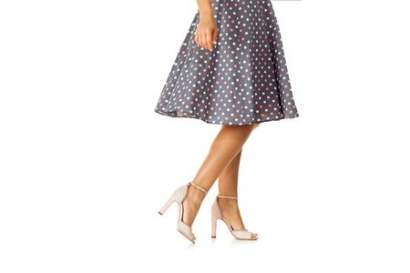 Woman in polka-dot dress standing in shoes isolated on white background. summer Stock Photo