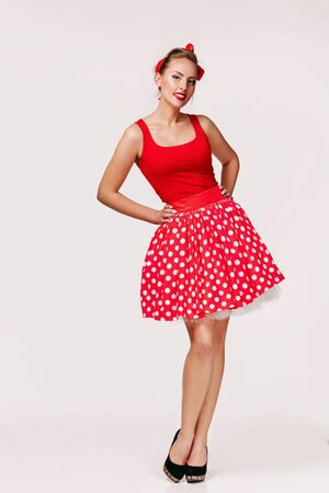 smiling pin up woman in polka dot red dress isolated on gray background. cute girl posing in retro style