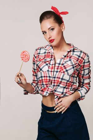 beautiful pin-up woman with pink lollipop on gray background Stock Photo - 128610773