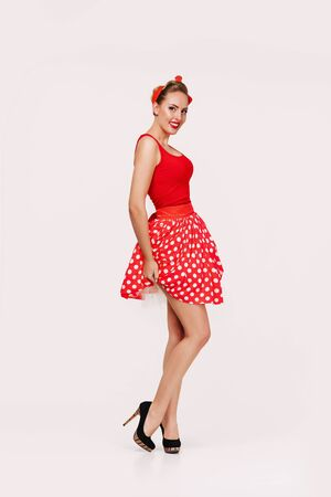 smiling pin up woman in polka dot red dress isolated on gray background. cute girl posing in retro style Stock Photo - 128610775