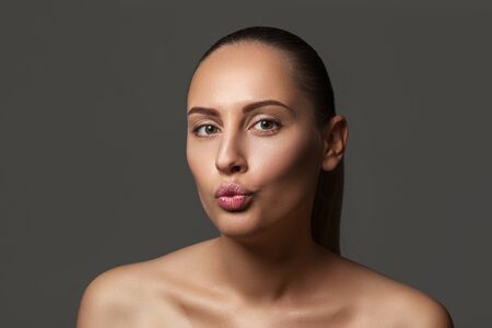 Portrait of cute woman sending blowing kiss with pout lips looking at camera isolated on dark background. Stock Photo