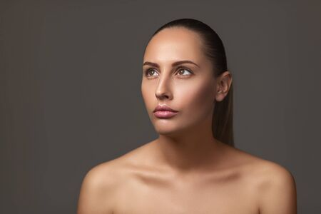 Beauty portrait of female face with natural perfect skin. model with light nude make-up on dark background. copy space Stock Photo - 128610778