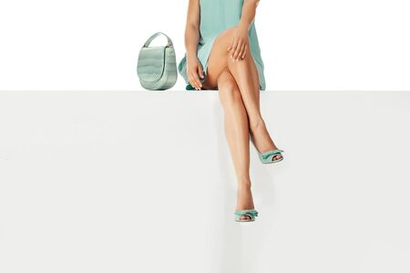 Beautiful legs woman wearing blue dress with blue purse hand bag, high heels shoes sitting on white bench. copyspace. Stock Photo
