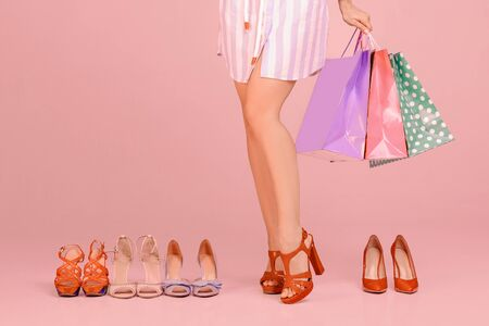 young woman with shopping bags stands between new pairs of shoes Stock Photo