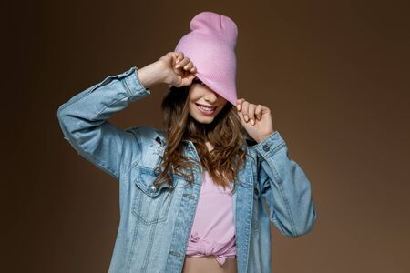 stylish beautiful woman in jeans jacket , a pink hat and stylish glasses posing on brown gold background. girl winks 版權商用圖片