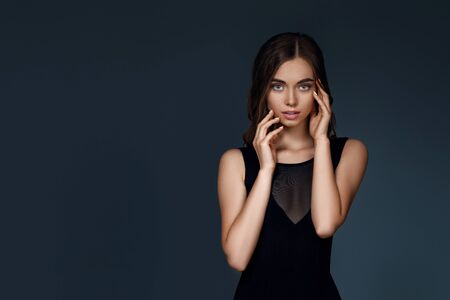 portrait of gorgeous elegant woman with perfect skin and long hair in black dress on dark background. girl looking at camera. copy space Stock Photo