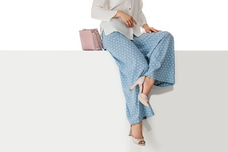 Beautiful legs woman wearing polka-dot blue pants and pink high heels shoes sitting on white bench. with copyspace. Stock Photo