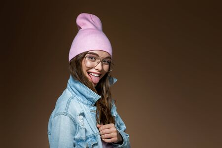 funny beautiful woman in jeans jacket , a pink hat and stylish glasses shows tongue. copyspace