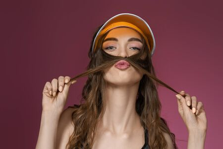 portrait of funny woman in orange sun visor fooling around on pink background. girl looking at camera. summer time