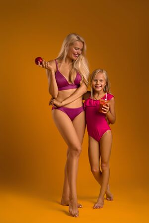 blonde woman mom in a swimsuit holds an apple and her daughter in a swimsuit drinks fresh juice. healthy life