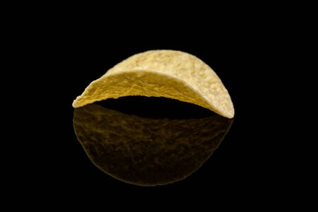 Salty delicious potato chips isolated on black background