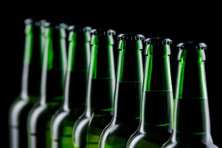Row of glass bottles of beer on dark background Stock Photo