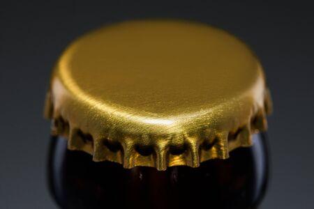 gold cap of beer bottle on dark background