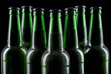 Row of wet glass bottles of beer on dark background