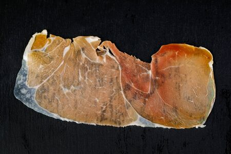prosciutto on a black background, top view. ham on stone board