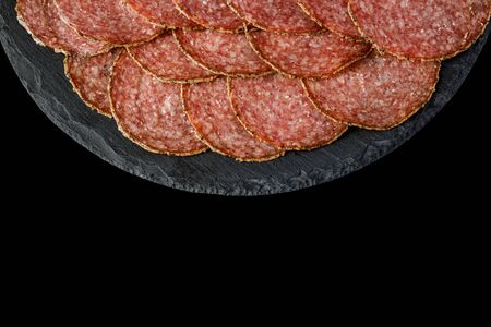 Plate with delicious sliced sausages on stone board. copy space. top view