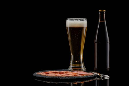 beer bottle, glass of beer and delicious sliced sausages on stone boardon black background. copy space