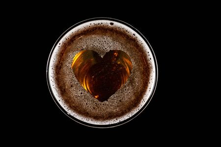 heart shape on foam in glass of beer on black background Top view
