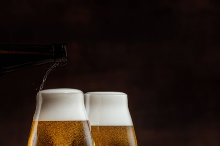 two glasses of cold golden beer on a dark background. copy space. pouring beer into glass