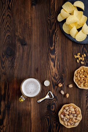 Beer glass with bottle cap and snack on wood background. top view. copy space