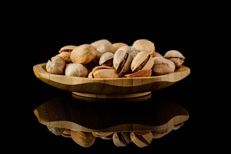 wooden plate of salted pistachio nuts on black background.