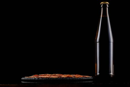 glass beer bottle and delicious sliced sausages on stone boardon black background. copy space Stock Photo