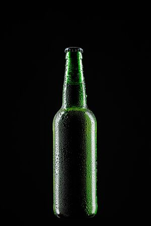 wet glass bottle of beer isolated on black background