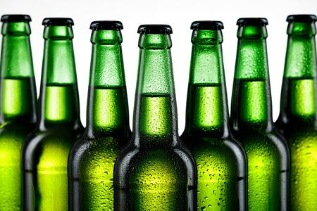 Row of glass bottles of beer on white background