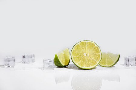Ice cubes and lime wedge on white background Banco de Imagens