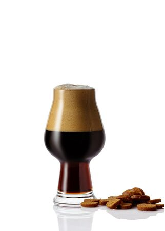 Perfect glass of dark beer with foam and dry bread bruschetta on white background