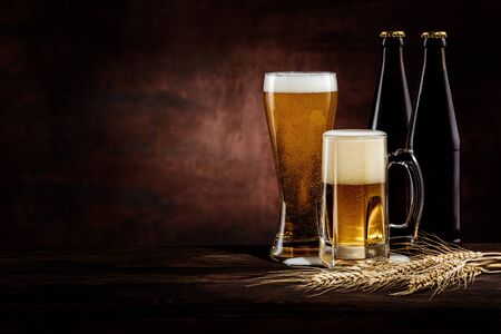 Bottle and two glasses of cold golden beer and wheat spikelets on dark background. copy space