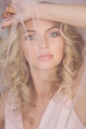 Porträt einer schönen lockigen blonden Frau mit Schleier in wunderschönem rosa Kleid