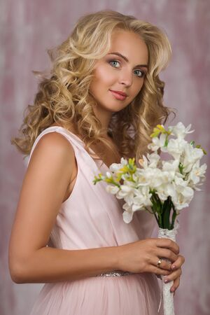 portrait of beautiful curly blonde bride in gorgeous pink dress with flower