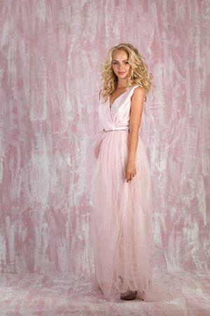 beautiful curly blonde woman bride in chic pink dress