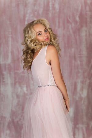 portrait of beautiful curly blonde woman in gorgeous pink dress Banco de Imagens