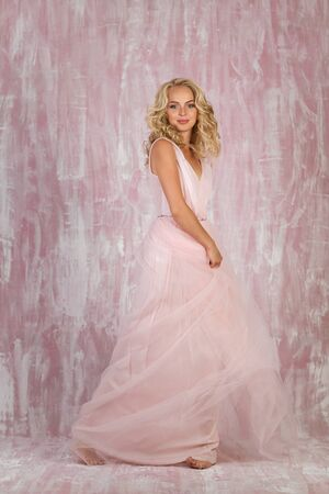 beautiful happy curly blonde woman bride in chic pink dress Stok Fotoğraf