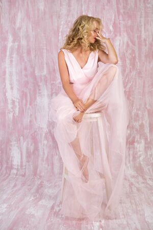 beautiful curly blonde woman in chic pink dress posing on chair
