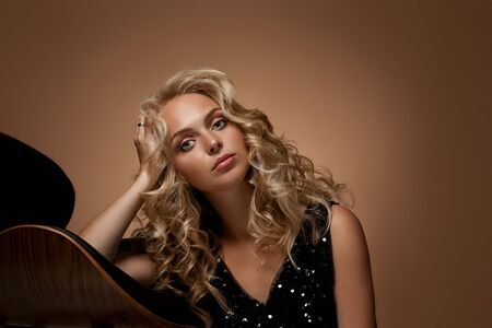 portrait of beautiful curly blonde fashion woman in gorgeous black dress posing on gold dark background
