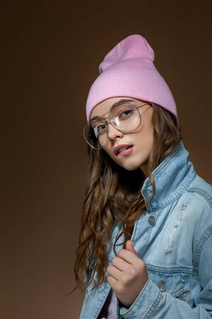 stylish beautiful woman in jeans jacket , a pink hat and stylish glasses posing on brown gold background Banco de Imagens