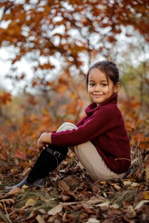 Fashionable kid 5 year old posing in autumn park. little girl sitting in fallen leaves