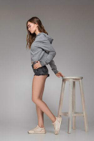 fashion attractive woman with long hair in sweater posing on chair on gray background.