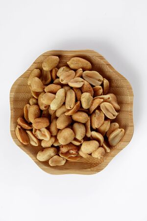 wood plate of salted peanuts isolated on white background. snack to beer Banco de Imagens