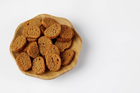 wood plate of brown crusty bread bruschetta on white background. top view