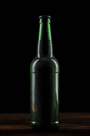 wet glass bottle of beer on wood table