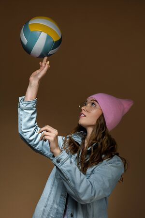 cute hipster girl in jeans, a pink hat and stylish glasses with a ball posing in the studio Banco de Imagens