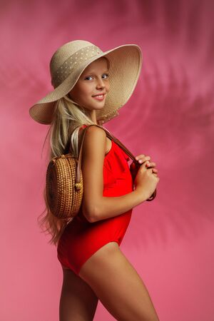 cute little child girl in a red swimsuit and hat posing on a pink background. summer time
