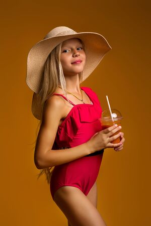 cute fashion little child girl in a red swimsuit and hat with fresh juice posing on orange background. summer time Banco de Imagens