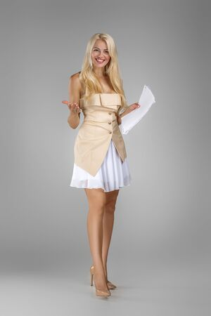 beautiful blond woman in dress holding paper documents on gray background